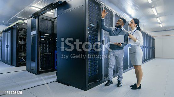 1131198396istockphoto Black IT Technician with a Laptop Computer Gives a Tour to a Young Intern. They Talk in Data Center while Walking Next to Server Racks. Running Diagnostics or Doing Maintenance Work. 1131198425