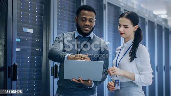 1131198396istockphoto Black IT Technician with a Laptop Computer Gives a Tour to a Young Intern. They Talk in Data Center while Walking Next to Server Racks. Running Diagnostics or Doing Maintenance Work. 1131198426