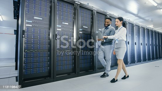 1131198396istockphoto Black IT Technician with a Laptop Computer Gives a Tour to a Young Intern. They Talk in Data Center while Walking Next to Server Racks. Running Diagnostics or Doing Maintenance Work. 1131198427