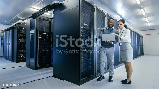 1131198396istockphoto Black IT Technician with a Laptop Computer Gives a Tour to a Young Intern. They Talk in Data Center while Walking Next to Server Racks. Running Diagnostics or Doing Maintenance Work. 1131198439
