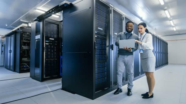 Schwarzer IT-Techniker mit einem Laptop-Computer gibt eine Tour für eine junge Praktikant. Sie sprechen im Rechenzentrum, während sie als Nächstes zu Server-Racks gehen. Laufende Diagnostik oder Wartungsarbeiten. – Foto