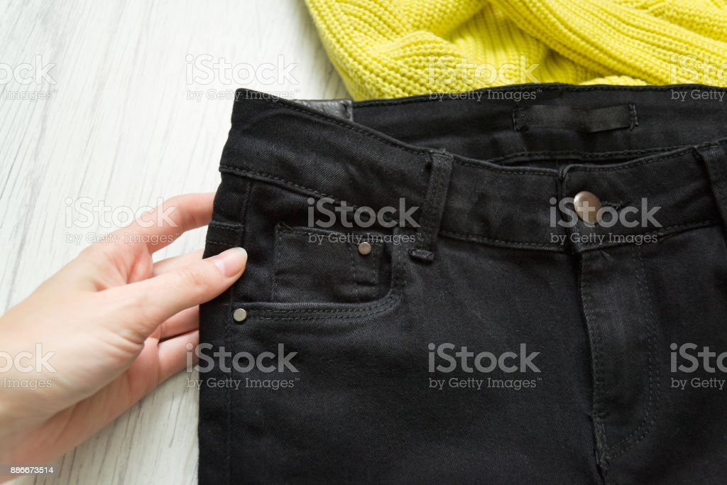 Black jeans in a female hand. Fashionable concept. Close up stock photo