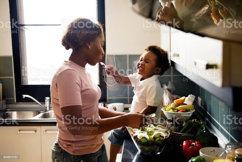 Black kid feeding mother with cooking food in the kitchen stock photo