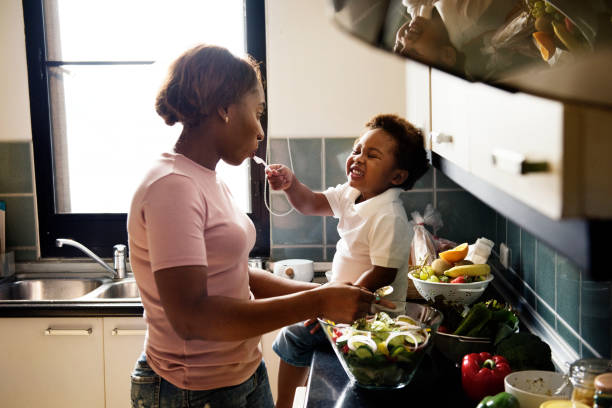 black kid feeding mother with cooking food in the kitchen - kids cooking stock photos and pictures