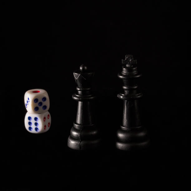 black king and queen next to dice on a dark background stock photo
