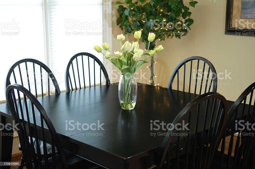 Black kitchen table with floral centerpiece seating six royalty-free stock photo