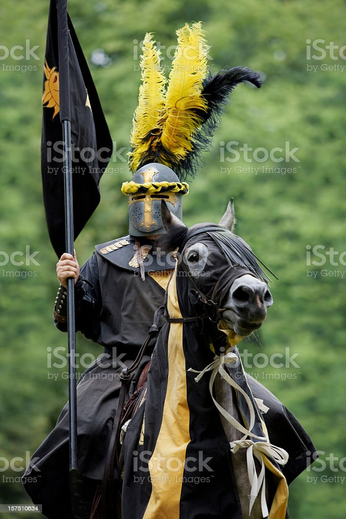 Black knight in suit of armor on horse stock photo