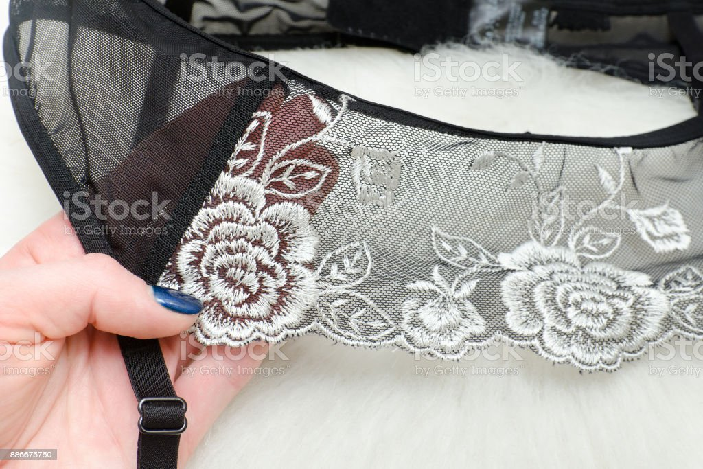 Black lace belt for stockings in female hand. Fashionable concept stock photo