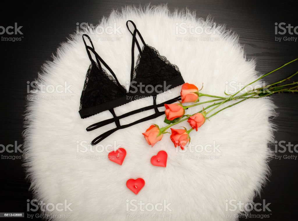 3125bc233 Black lace bra on white fur and a bouquet of orange roses. Fashionable  concept. Top view - Stock image .