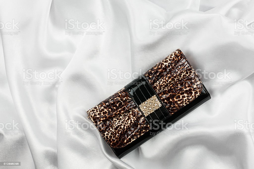 Black lacquer bag inlaid with diamonds lying on a white stock photo