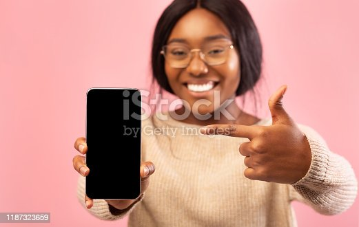 1132512759 istock photo Black Lady Showing Phone Blank Screen Standing, Pink Background, Mockup 1187323659