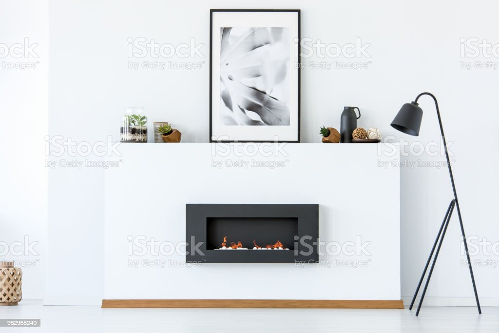 Black lamp next to fireplace and poster in white minimal living room interior. Real photo
