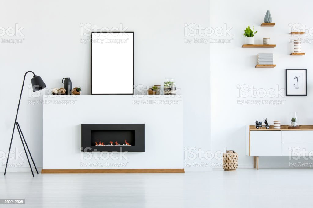 Black lamp next to fireplace in white living room interior with mockup of empty poster. Real photo stock photo