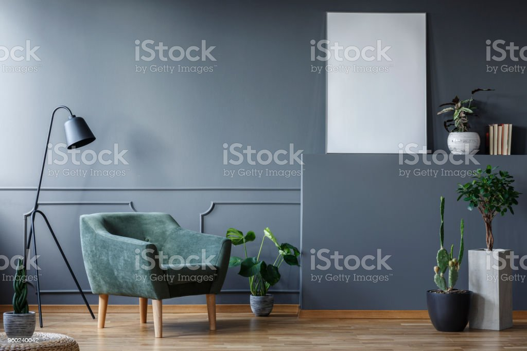 Black lamp next to green armchair in living room interior with plants and mockup of poster stock photo