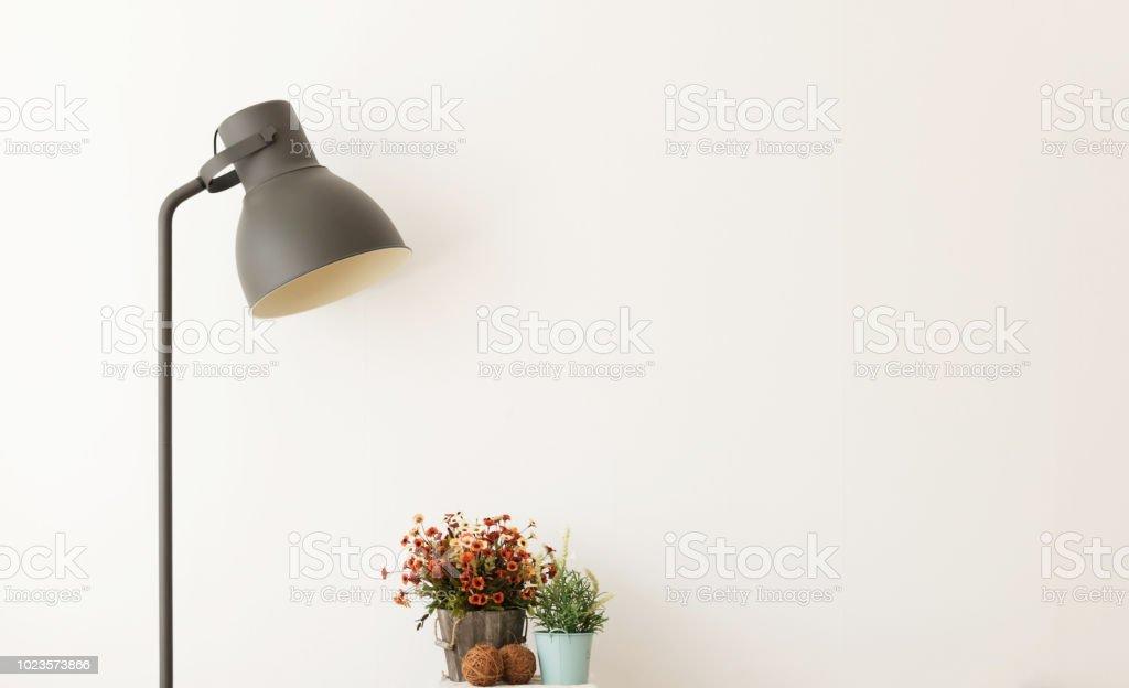 Black lamp with vase of flower on desk in modern room on white...