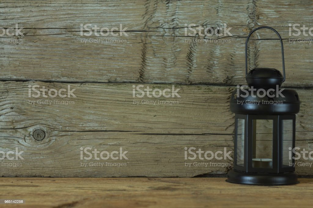Black lantern on a background of old wooden boards. Abstraction. Concept. zbiór zdjęć royalty-free