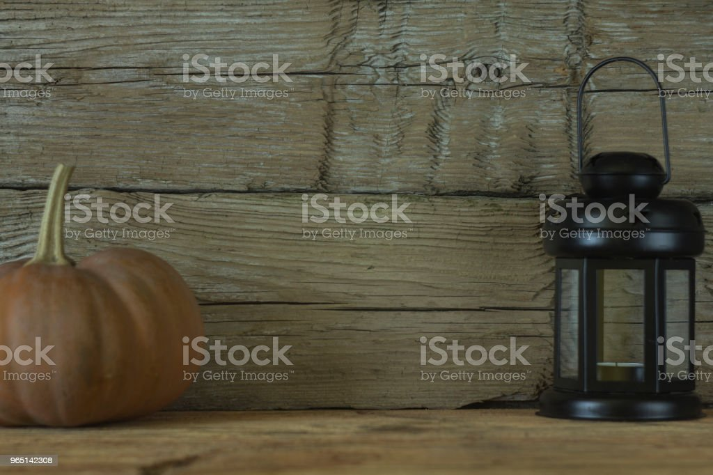 Black lantern with a pumpkin on a background of old wooden boards. Halloween. Abstraction. Concept. zbiór zdjęć royalty-free
