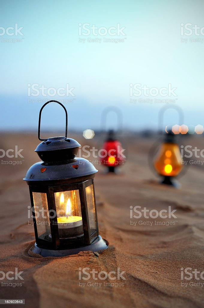 Black lantern with candle on desert sand royalty-free stock photo