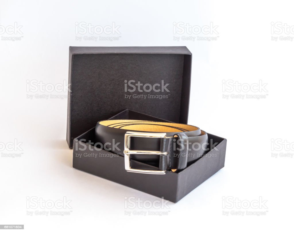 Black leather belt with metal buckle and its black cardboard packing box on white background royalty-free stock photo