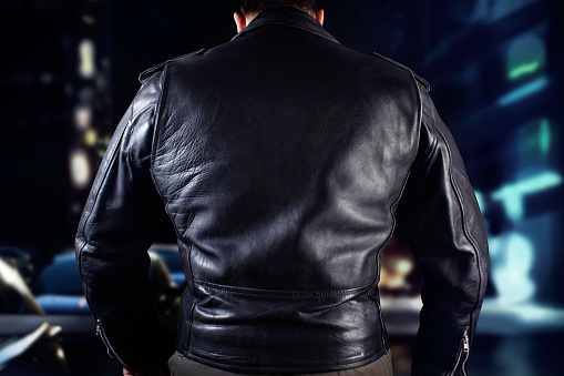 Black leather biker in jacket standing on night citylights background.