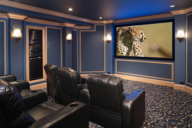 Black leather chairs adorn a beautiful home theatre. Black leather chairs anchor a luxury theatre in a residential home.  man cave stock pictures, royalty-free photos & images