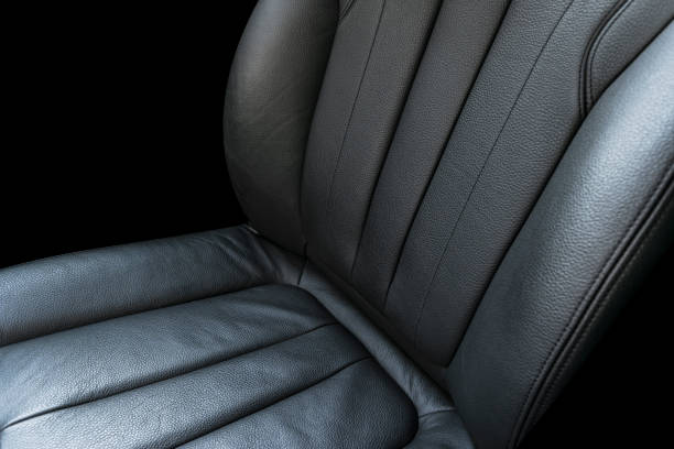 Black leather interior of a car. Perforated Leather comfortable seats with yellow stitching isolated on black background. Car interior details. Car detailing. Car inside stock photo