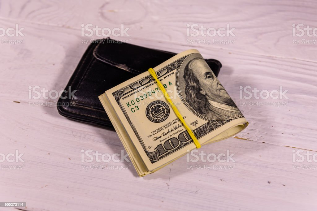 Black leather money clip with the one hundred dollar bills on wooden table zbiór zdjęć royalty-free