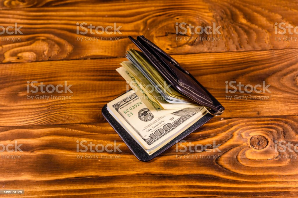 Black leather money clip with the one hundred dollar bills on wooden table royalty-free stock photo