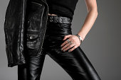 Person wearing black leather pants and jacket with zippers.