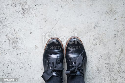 Black leather shoes. A pair of vintage fashion leather shoes for lady on the concrete floor, top view.