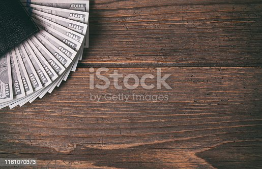 Black leather wallet and one hundred dollar banknotes on the rustic wooden background.