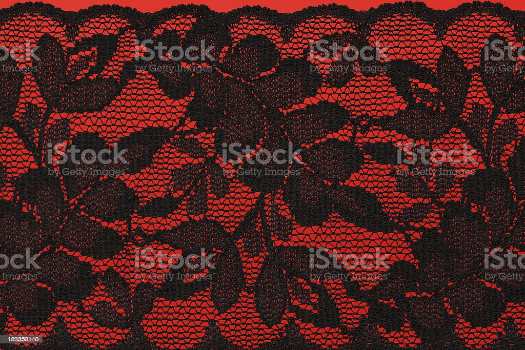 Black lingerie lace on a red background royalty-free stock photo