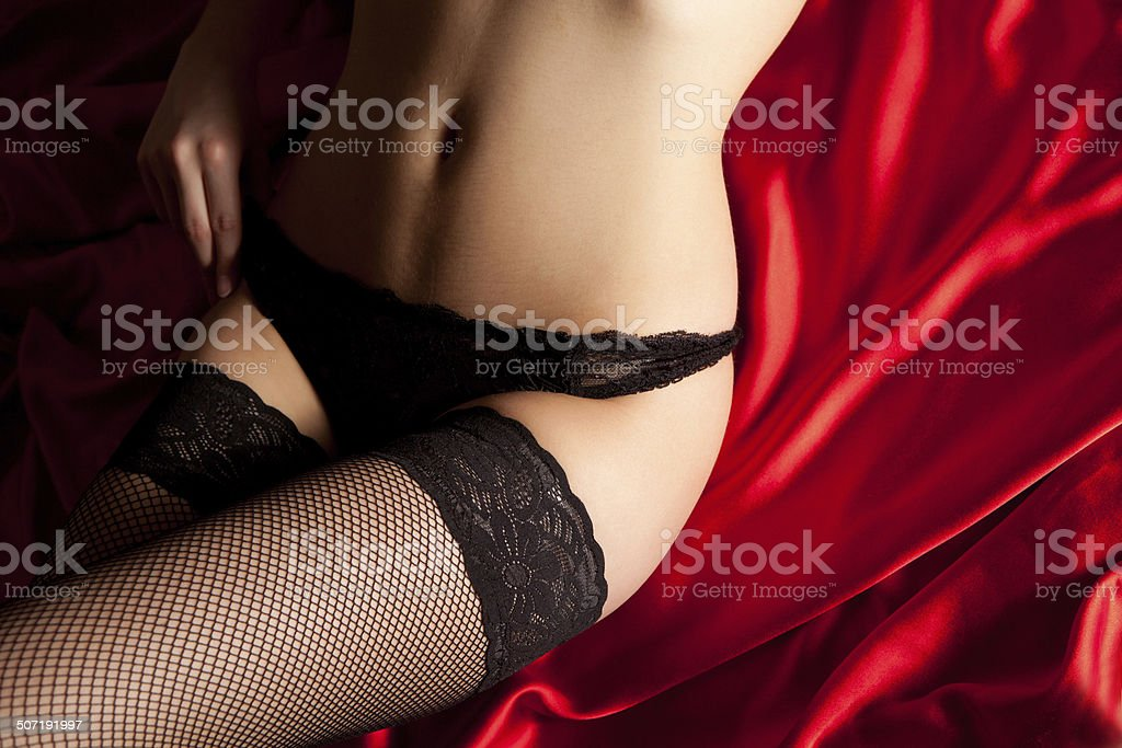 Black lingerie on red silk stock photo