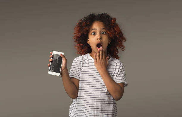 black little girl with crashed mobile on gray background - kids phones stock photos and pictures
