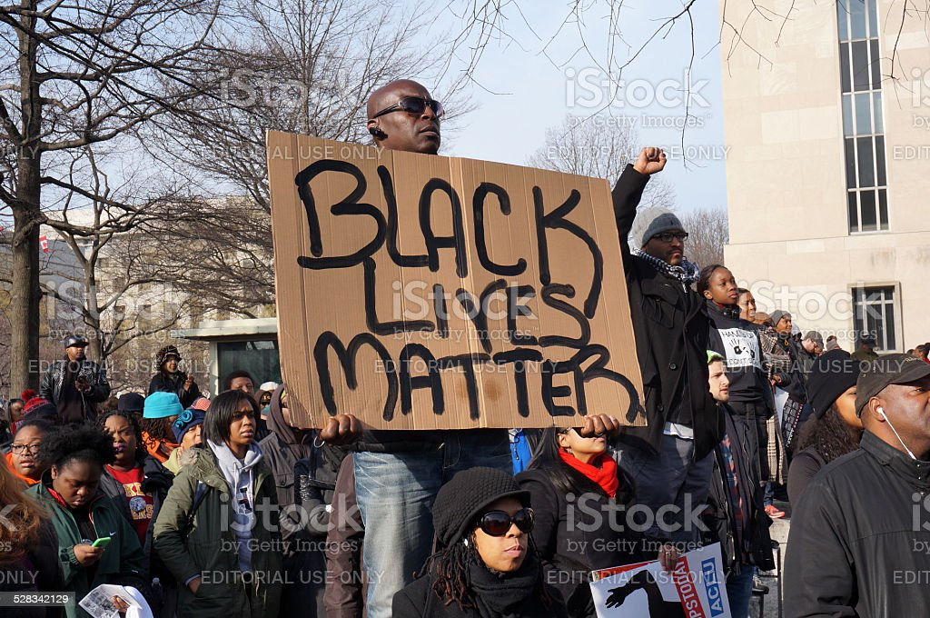 Black Lives Matter Washington DC, USA-December 13, 2014: This man is protesting police brutality at a protest led by Reverend Al Sharpton on Pennsylvania Avenue in Washington DC. He displays a sign with the message Black Lives Matter.  Recently the deaths of Michael Brown, Eric Garner and Tamir Rice have upset the black community. African Ethnicity Stock Photo