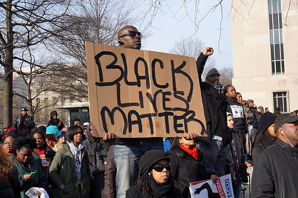 Black Lives Matter Washington DC, USA-December 13, 2014: This man is protesting police brutality at a protest led by Reverend Al Sharpton on Pennsylvania Avenue in Washington DC. He displays a sign with the message Black Lives Matter.  Recently the deaths of Michael Brown, Eric Garner and Tamir Rice have upset the black community. protest stock pictures, royalty-free photos & images