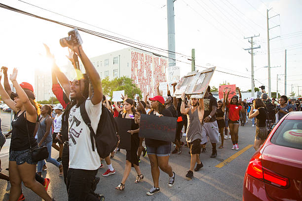 Black Lives Matter protest Miami Miami, United States - July 9, 2016: Group of peaceful protestors holding black lives matter related content march on the streets of Miami in the design district. protest stock pictures, royalty-free photos & images