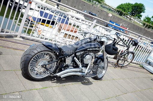 Black low seated Harley Davidson motorcycle with big exhausts standing and parked in Media Harbor Duesseldorf above yachts in background