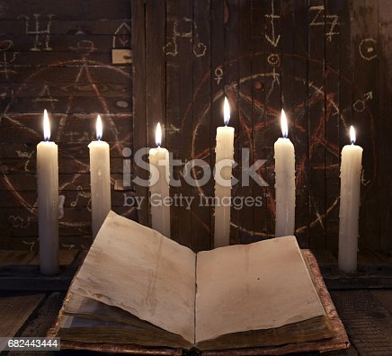 811119304 istock photo Black magic ritual with burning candles and open book 682443444