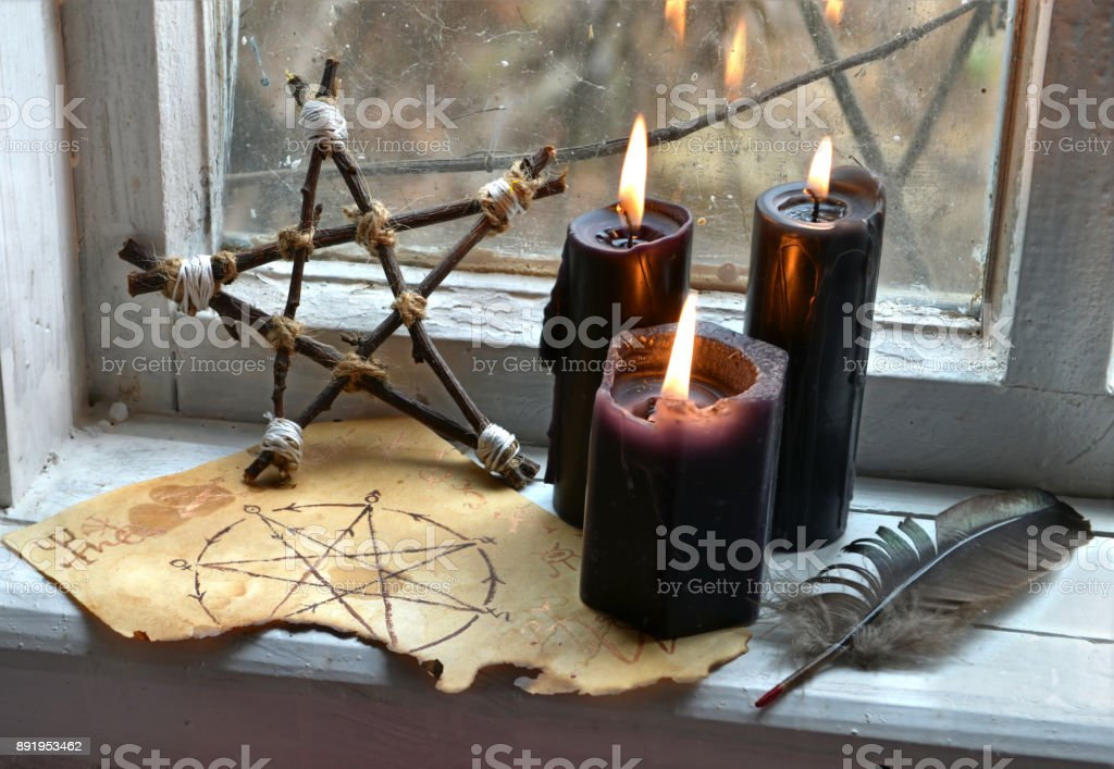 Black magic ritual with pentagram and black candles stock photo