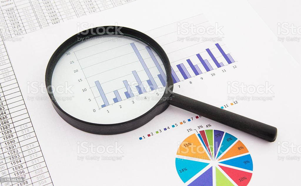 Black magnifier on a business paper with charts and graphs royalty-free stock photo