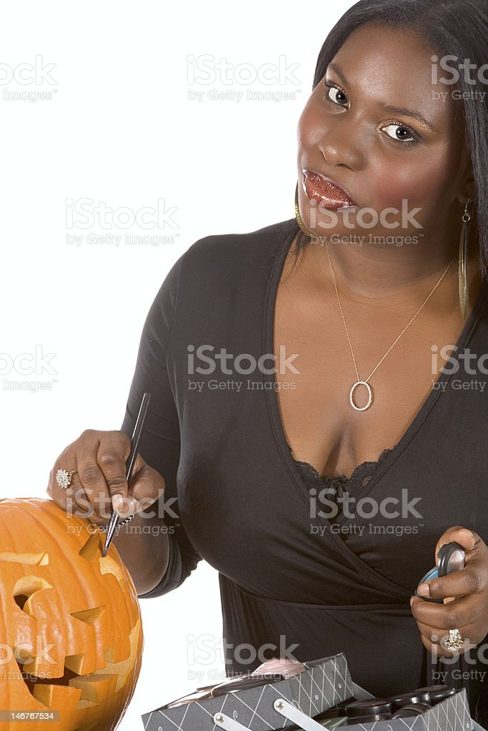 Black make-up artist decorating Halloween pumpkin royalty-free stock photo