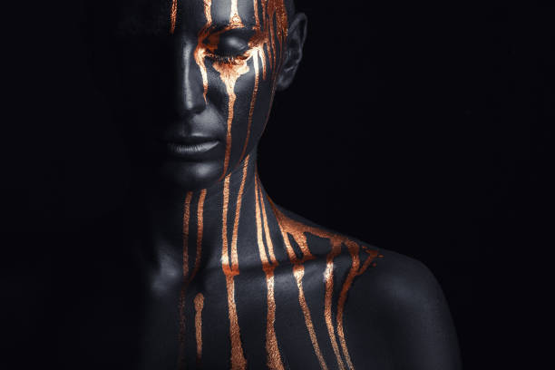 Black makeup Art fashion makeup. An amazing woman with black makeup and leaking gold paint body paint stock pictures, royalty-free photos & images
