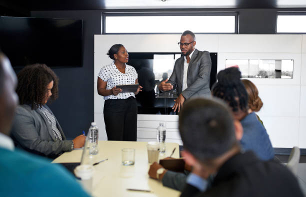 Black male and female businesspeople presenting to diverse multi-ethnic coworkers in office space with laptop and tablet stock photo