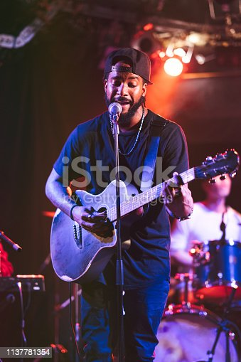 A black male guitarist is singing and playing the acoustic guitar on stage.