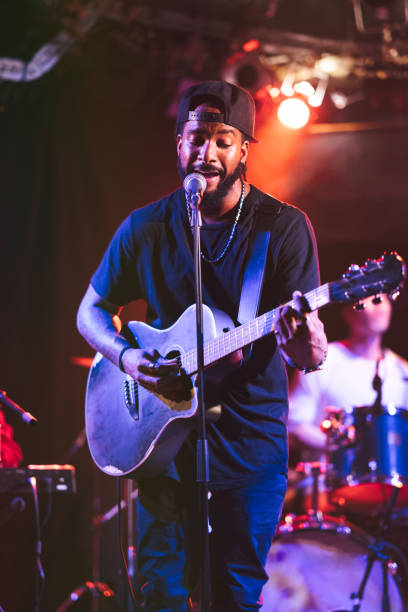 Black male guitarist singing and playing acoustic guitar on stage stock photo
