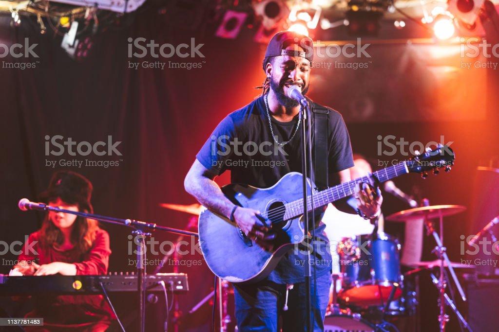 Schwarzer Gitarrist, der auf der Bühne singt und Akustikgitarre spielt - Lizenzfrei Afrikanischer Abstammung Stock-Foto