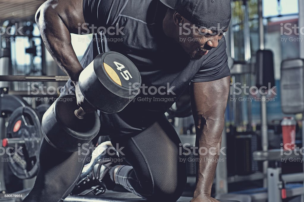 black male lifting dumbbells at a gym stock photo