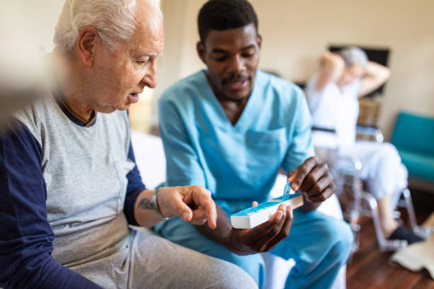 Schwarze männliche Krankenschwester gibt Anweisungen an Senior-Patienten, wenn seine Pillen zu nehmen – Foto