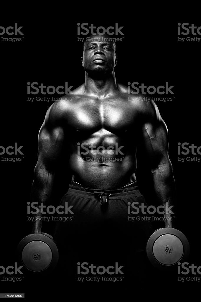Black male posing with naked torso holding dumbbells stock photo